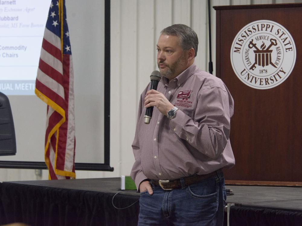 Man speaks into a handheld microphone. Background includes the Mississippi State University seal and an American flag.