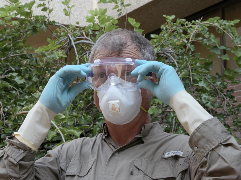 A man in a brown shirt, safety mask and rubber gloves adjusts a pair of goggles over his eyes.