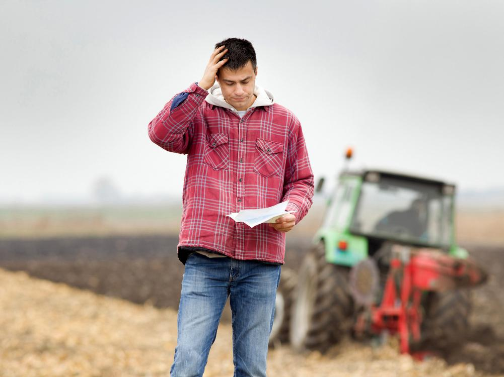 A farmer stands with a tractor in the background looking at a document and holding a hand to his head in worry.
