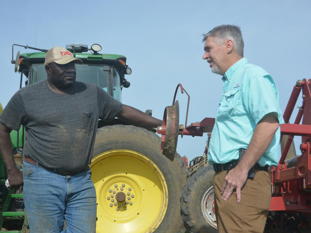 Two men facing each other in conversation and standing beside a tractor and equipment with a clear, blue sky overhead.