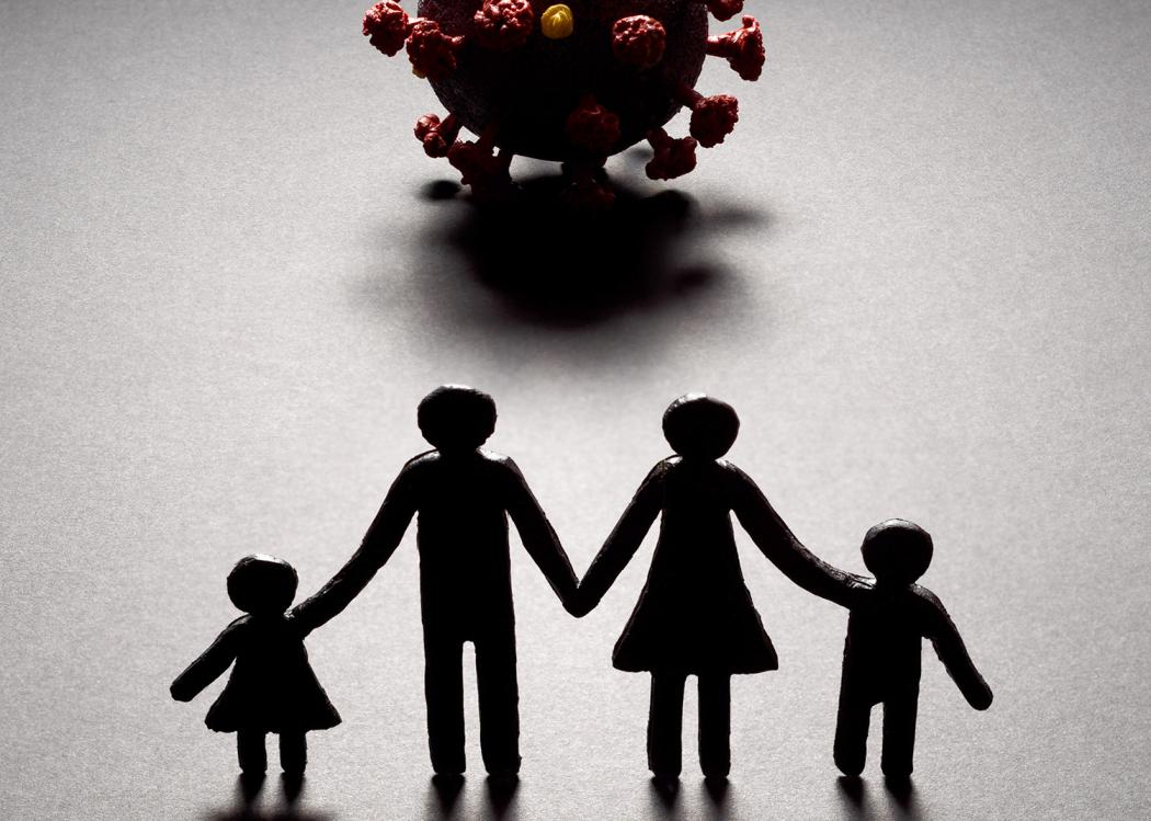 Silhouette of a paper cut-out style family of four facing a three-dimensional model of the novel coronavirus.