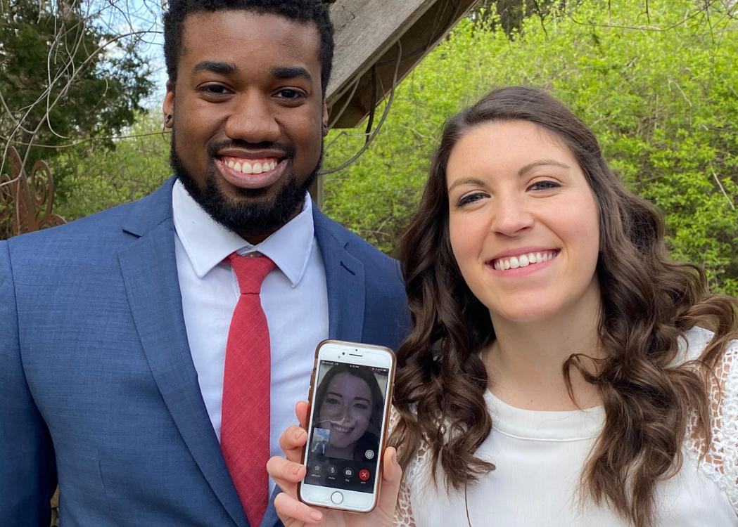 A smiling couple holds a smart phone showing a woman on a video call.