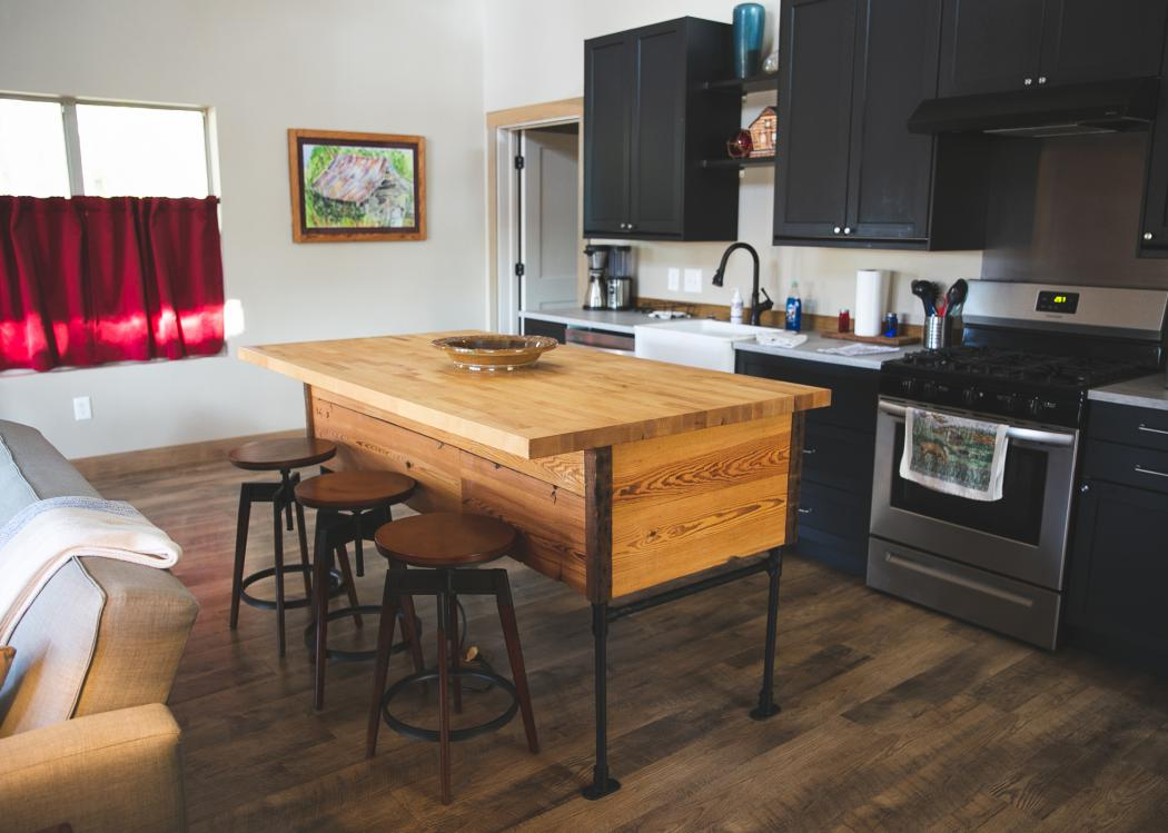 A serving island and three stools sit in a kitchen.