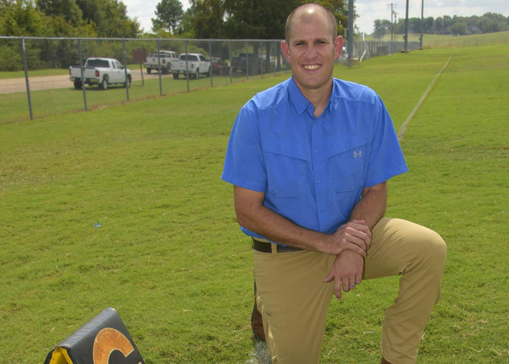 A man kneels on a football practice field beside a football.