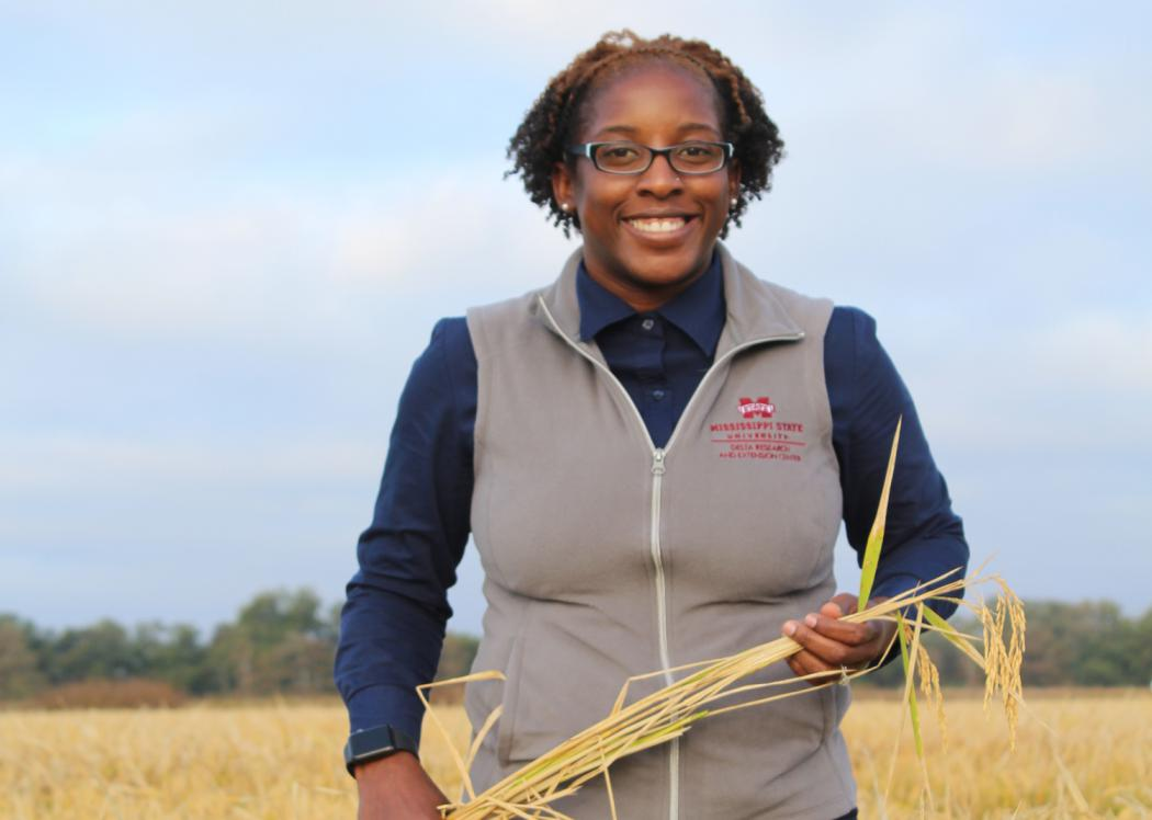 A woman holds a stalk of grain while standing in a field.