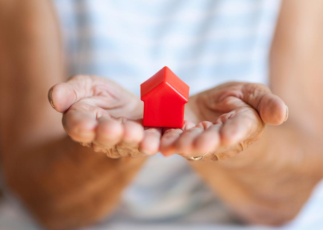 A small red toy house rests in a woman's open hands.