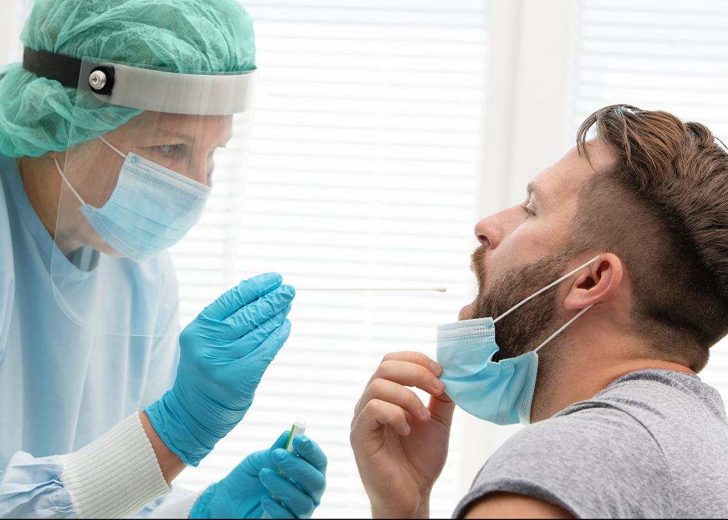 Medical worker in protective clothing takes a throat swab from a male patient.
