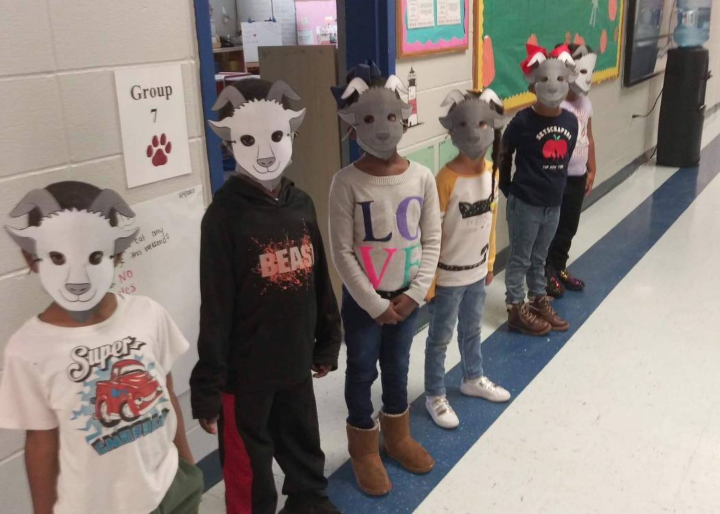 Six children stand in a hallway wearing paper masks depicting billy goats.