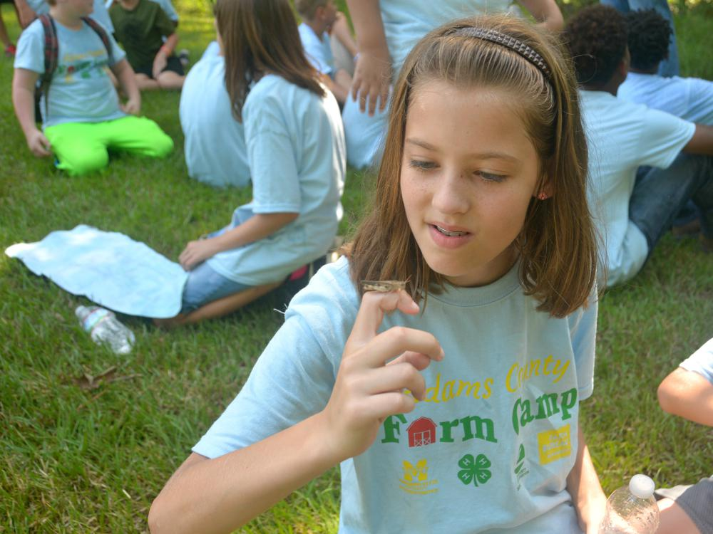 Adara Blalock, 10, visits with a grasshopper (or vice versa) while taking a break during the Adams County Farm Camp near Natchez, Mississippi, on July 7, 2016. (Photo by MSU Extension Service/Linda Breazeale)