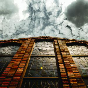 Worm's eye view of building with stained glass windows with cloudy sky.