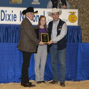 A teenage girl stands in between two men wearing cowboy hats and holding a plaque in front of her.
