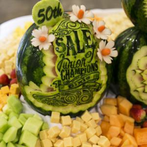 """A green watermelon with the words """"50th Sale of Junior Champions Dixie National"""" and other designs rests in the middle of assorted bite-sized foods."""