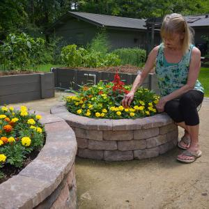 A woman wearing a blue tank top kneeling down next to a circular brick planter filled with yellow and red flowers.