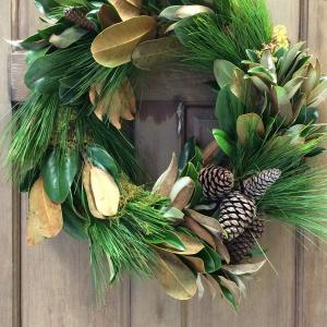 A magnolia and pine wreath on a wooden door.