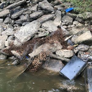 Trash piled up on a rocky bank at the edge of shallow water.