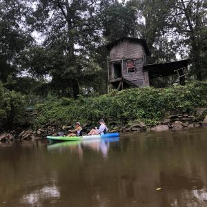Two women paddling a green, white, and blue kayak in front of an old wooden building on top of a grassy bank at the edge of water.
