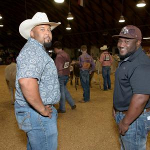 Two men stand together in the livestock show ring at the Mississippi State Fair.