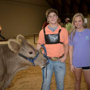 A teenage boy and girl stand beside a cow at the Mississippi State Fair.