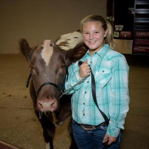 A young girl stands beside a cow at the Mississippi State Fair.