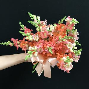 A bridesmaid's bouquet of coral-colored snapdragons with bow.