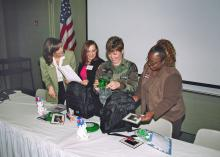 4-H Military Project coordinator Whitney Mathis, from left, provides military wives Marianne Breland and Melissa Tanksley with Hero Packs containing special items to show support of children with parents deployed in Operation Iraqi Freedom. Sheran Watkins, 4-H youth agent in Harrison County, also looks at the materials designed to lift the spirits of children missing their loved ones.