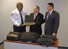 Dr. Vance Watson, MSU Extension Director, presents a used computer to Bolton Police Chief Michael Williams. Watson presented the equipment with Jay Ledbetter, director of the Mississippi Department of Homeland Security. (Photo by Ned Browning)