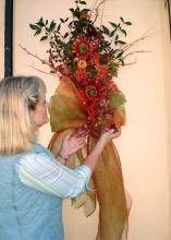 Create unique decorations and gifts for less using resources from gardens, fields and woods. Lelia Kelly puts the finishing touches on a door swag she made using crape myrtle seed pods, nandina foliage and berries, English ivy and bare branches, highlighted with silk sunflowers and other silk materials. (Photo by Vickie McGee)
