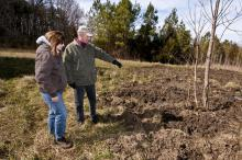 USDA Mississippi Wildlife Services Director Kris Godwin and Paul Sellars, a tree farmer in Oktibbeha County, assess damage on Sellars' property caused by wild pigs. The pigs' deep rooting has made it difficult for Sellars to maintain parts of his land. (Photo by Scott Corey)