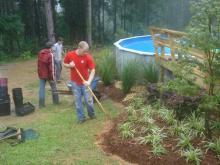 Mississippi State University's Landscape Architecture Delegates volunteered to help the family of a young girl with a serious nerve disorder. David Russell, Dustin Randall and Dale Brasher place plants around the family's pool to keep the soil intact. With the erosion problem solved, the girl can continue her regular pool therapy to ease her chronic pain.