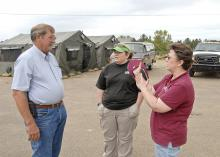 Choctaw County supervisor Archie Collins, left, discusses the day's schedule with MSU Extension Service food and nutrition assistant Dee Ann Williams and volunteer Ashley Williams at the Mill Springs disaster response center in Choctaw County. (Photo by Bob Ratliff)