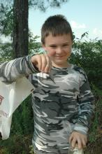 Corran Hall , 9, a fifth grader from Des Moines, Iowa, displays a dragonfly he caught during the insect and plant ecology camp at Mississippi State University.