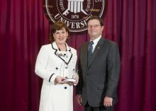 Deputy State Veterinarian and Public Health Veterinarian Dr. Brigid Elchos, left, accepts her alumnus of the year award from Dr. Kent Hoblet, dean of Mississippi State University College of Veterinary Medicine. Elchos received the honor because of her outstanding achievements and leadership. (Photo by MSU University Relations/Megan Bean)