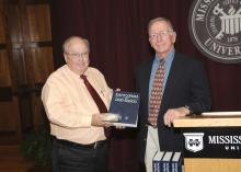 Mississippi State University professor emeritus John Fuquay (right) presents a copy of the first edition the Encyclopedia of Dairy Science and a CD-ROM of the second edition to Terry Kiser, head of MSU's animal and dairy sciences department. Fuquay was recently honored for his work as editor-in-chief of the second edition of the encyclopedia. (Photo by Scott Corey)