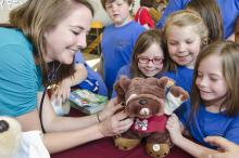 Alex Long (back, left) looks on as (left to right) Maddi Capps, Abby Hood and Addi Capps from Mooreville Elementary School present a bulldog to Mississippi State University College of Veterinary Medicine student Janet Koester. Koester and her classmates tended to injured toys on April 13 at the teddy bear clinic, part of CVM's annual open house celebration. (Photo by MSU College of Veterinary Medicine/Tom Thompson)