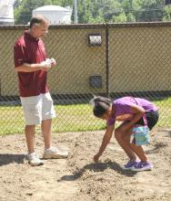 Lowndes County Extension Service horticulturist Jeff Wilson measures the appropriate spacing and hands out squash seeds to be planted by military youth such as 10-year-old Keyanna Dooley. They recently planted a Welcome Home Garden for veterans at the Columbus Air Force Base youth center. (Photo by MSU Ag Communications/Scott Corey)