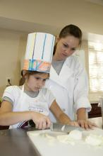 Camper Kendall Willeford of Starkville and Kristin Weaver of Byhalia, a student in the Food Science, Nutrition and Health Promotion program at Mississippi State University, prepare the ingredients for a dish during Fun with Food. (Photo by MSU Ag Communications/Kat Lawrence)