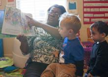 Child-care provider Dana Smith reads a book to Levi Mills and Jakob Reyes during story time at her in-home child-care program in Olive Branch. Busy Bundles of Joy Learning Center was recently recognized as a 5-star center by the in-home Quality Rating and Improvement System. (Photo by MSU Extension Service/Alicia Barnes)