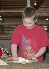 Riley Mann, 9, a third-grader from Marietta, uses his hands to smash a banana on April 18, 2013, as part of an activity using toys and fruit to demonstrate for the class how a tree is turned into paper. (Photo by MSU Ag Communications/Kat Lawrence)