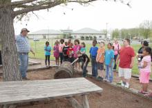 Benton County Extension agent Michael Pruitt explains how pine trees are turned into the cardboard boxes used in pizza delivery. The students were touring Mississippi State University's Pizza Farm in Verona on April 18, 2013. (Photo by MSU Ag Communications/Kat Lawrence)