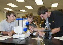 Gage Hensarling, 11, left, and Jac Cooper, 10, watch Edward Entsminger extract a plant disease sample to examine under the microscope. The group were participating in Mississippi State University's weeklong Bug and Plant Camp. (Photo by MSU Ag Communications/Kat Lawrence)