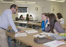 Charles Freeman, assistant professor in the Mississippi State University Apparel, Textiles and Merchandising program, looks at a sketch of a garment with Sarah Ashley Bealor, left, a senior from Tampa, and Rachel Buchanan, a senior from Pontotoc. (Photo by MSU Ag Communications/Kat Lawrence)