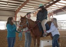 Lori Irvin, a therapeutic riding volunteer, holds the horse still while Mississippi State University Extension Service agents Jim McAdory and Cassie Brunson make sure Martina Tubby is comfortable for a ride at the Elizabeth A. Howard 4-H Therapeutic Riding and Activity Center in West Point on March 20, 2014. (Photo by MSU Ag Communications/Kat Lawrence)