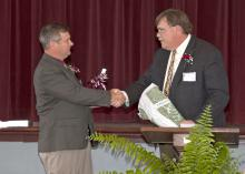 Mississippi State University Extension Service Director Gary Jackson, right, presents Forrest County Agricultural High School Superintendent Jerry Morgan with an MSU cowbell April 8, 2014, to mark the beginning of a partnership between the school and university. The Extension Service loaned the school an interactive video system that allows students, faculty and staff to attend Extension educational programs. (Photo by MSU Ag Communications/Kat Lawrence)