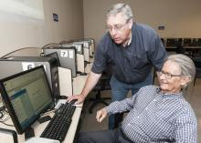 As part of an ongoing program of computer skills workshops, John Giesemann with the Mississippi State University Extension Service Center for Technology Outreach shows Vern Boothe how to access a slideshow program at the WIN Job Center in Madison on July 9, 2013. (File photo by MSU Ag Communications/Scott Corey)
