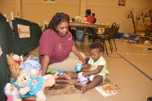 Miski Brown, a Mississippi State University Extension Service staff member with the Mississippi Child Care Resource and Referral Network, keeps Maylasia Haynes active while her family is in the American Red Cross Shelter at First Baptist Church in Louisville, Mississippi, on May 1, 2014.  (Photo by MSU Ag Communications/Linda Breazeale)
