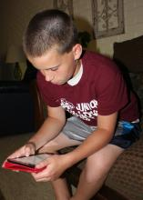 David Coblentz, 12, uses a search engine on an iPad mini. Parents should take some practical steps to help ensure their children are protected as they use Internet-connected devices to socialize or do homework. (Photo by MSU Communications/Bonnie Coblentz)