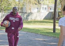 Mississippi State University senior football player Robert Johnson plays basketball with one of the residents of Sally Kate Winters Family Services Emergency Shelter Program. (Photo by David Ammon/ College of Agriculture and Life Sciences)