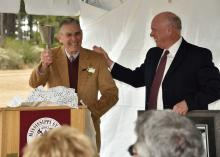 "E.G. ""Gene"" Morrison, left, rings the engraved cowbell given to him by George Hopper, director of the Mississippi State University Mississippi Agricultural and Forestry Experiment Station on Nov. 20, 2014, at the Brown Loam Branch Experiment Station. The station was renamed in honor of Morrison, who served as station superintendent for 33 years. (Photo by MSU Extension Service/Kevin Hudson)"