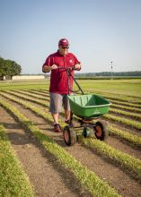 Barry Stewart, turf management specialist with the Mississippi Agricultural and Forestry Experiment Station, demonstrates fertilizing equipment on Aug. 29, 2013, on a recently cut patch of St. Augustine grass grown at Mississippi State University's R.R. Foil Research Center. (Photo by MSU Ag Communications/Scott Corey)