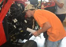 Rankin County 4-H member Robert Herrington takes a close look under the hood of a tractor as he identifies engine parts during a portion of the tractor competition on June 1, 2017. More than 700 4-H members took part in contests, workshops, tours and entertainment during their annual state meeting at Mississippi State University. (Photo by MSU Extension Service/Linda Breazeale)